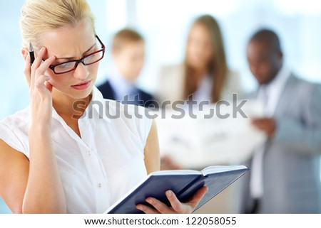 Portrait of anxious secretary looking into notepad and touching her head