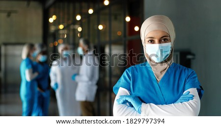 Portrait of Arab woman doctor in hijab, medical mask and gloves standing in hospital. Muslim female medic in traditional headscarf in clinic. Covid-19. Arabian nurse. Coronavirus. Protected.