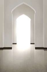 Portrait of arch door with tiled floor and white wall inside the mosque