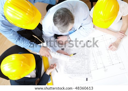 Portrait of architect explaining his project to co-workers