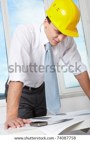 Portrait of architect in helmet looking at blueprint in office