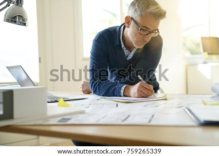 Portrait of architect in office working on blueprints