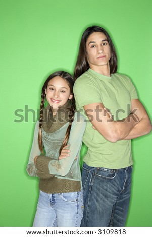 Portrait of Asian-American girl and teen boy standing back to back against green background.