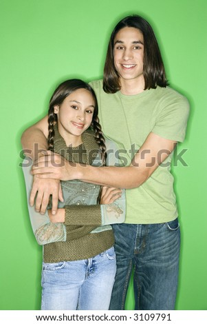 Portrait of Asian-American girl and teen boy standing with arms around eachother smiling against green background.
