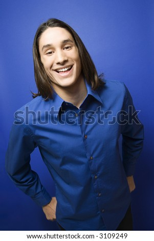 Portrait of Asian-American teen boy smiling at camera against blue background.