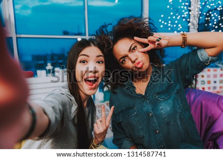 Portrait of asian and african women expressing fun. They clowning at camera. Fun concept
