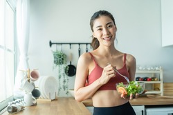 Portrait of Asian attractive woman hold salad bowl and look at camera. Beautiful sport girl in sportswear enjoy eat clean vegetables after exercise for health in house. Diet and Healthy food concept.