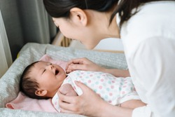 portrait of asian baby feeling comfortable after changing diaper and laughing to her mother happily. chinese woman is interacting with her kid on baby changing.
