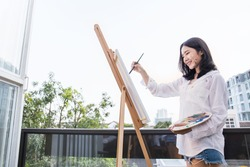 Portrait of asian beautiful woman paint in her art studio outdoor. Young asian girl holding her paintbrush. Artist workshop education concept