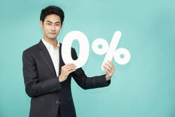 Portrait of Asian business man showing and holding 0% number or zero percent isolated over green background