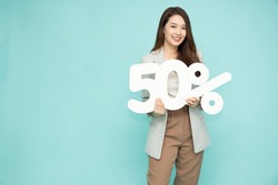 Portrait of Asian business woman showing and holding 50% number or Fifty percent isolated over light green background