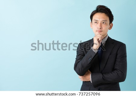 portrait of asian businessman isolated on blue background