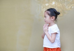 Portrait of asian child girl in traditional thai dress praying. Side view.