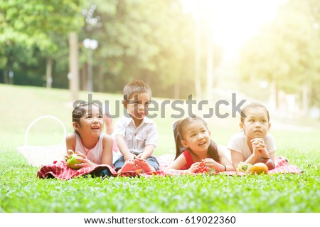 Portrait of Asian children picnics at park, lying on lawn. Little boy and girls having fun outdoors. Morning sun flare background.