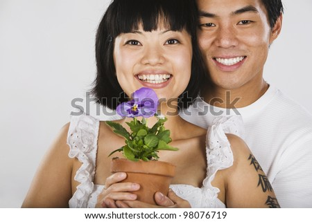 Portrait of Asian couple holding potted plant