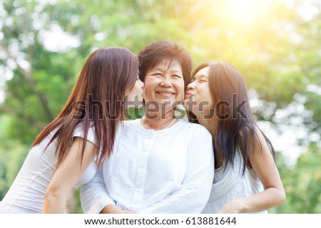 Portrait of Asian daughters kissing elderly mother, senior adult woman and grown child. Outdoors family at nature park with beautiful sun flare.