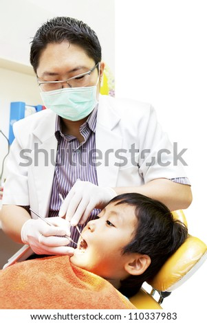 Portrait of asian dentist examining oral cavity of his patient at dental clinic