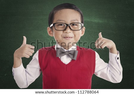 Portrait of asian elementary school student and thumbs-up. shot in the classroom