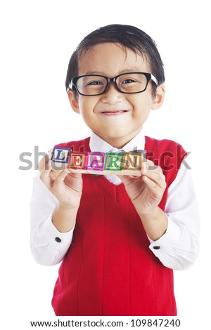Portrait of asian elementary school student showing letter blocks spelling out LEARN. shot in studio isolated on white