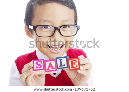 Portrait of asian elementary school student showing SALE word. shot in studio isolated on white