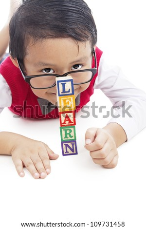 Portrait of asian elementary school student with tower of LEARN word. shot in studio isolated on white