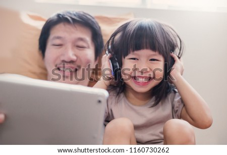 Portrait of Asian family father daughter look at a tablet computer on bed, little asian girl using laptop with dad. Weekend holiday leisure time education e-commerce online shopping concept (blur)