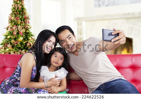 Portrait of asian family sitting on sofa and use a smartphone to take a self photo together
