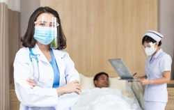 Portrait of Asian female doctor wearing medical protective face shield and mask looking at camera in arm crossed. nurse taking care of patient sickness on bed in hospital ward. new normal concept