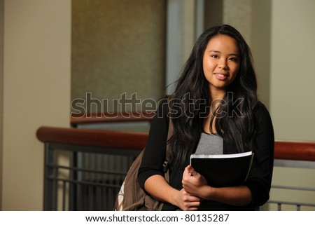 Portrait of Asian female student holding books indoors