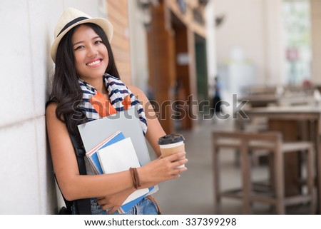 Portrait of Asian female student with textbooks and coffee