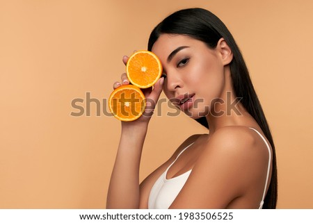 Portrait of Asian girl with shining clean skin of face holding orange halves in white underwear isolated on beige background. Vitamin C cosmetics concept Zdjęcia stock ©
