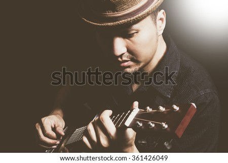 portrait of asian handsome guitarist playing acoustic guitar in unplug concert