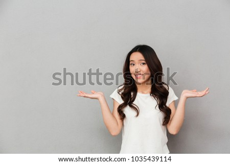 Portrait of asian indecisive woman with dark curly hair shrugging and throwing hands aside with clueless isolated over gray background