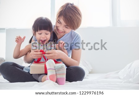 Portrait of asian little girl help her mother opening or wrapping gift box in bed room, celebration holiday Christmas mother's day card, love together celebrate happy family concept.