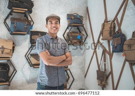 portrait of asian male business owner standing in front of his bag store