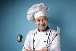 Portrait of Asian male chef shows ladle and spatula, ready to cook in the kitchen, kungfu chef in action