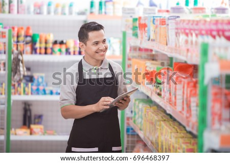 Portrait of asian male staff checking the product with tablet pc