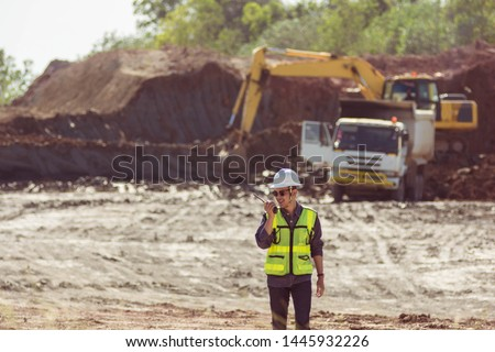 Portrait of asian male supervisor in mine soil field location operation a radio or walkie talkie to communication with co worker team with exavator and dumb truck digging  limestone as background