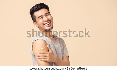 Portrait of Asian man showing his shoulder with bandage after getting a vaccination during covid-19 immunization program.