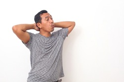 Portrait of Asian man standing while relax and whistling. Isolated on white background with copyspace