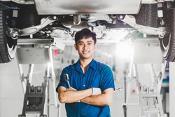 Portrait of Asian mechanic with repair equipment standing under the car in maintenance service center which is a part of showroom, technician or engineer professional work for customer