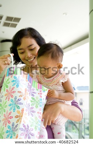portrait of asian mother and baby girl having fun shopping at the mall