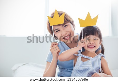 Portrait of asian mother and child daughter playing having fun together. Beautiful funny girl and mommy have crowns on sticks. Fun love family lifestyle single mom love mother's day holiday concept