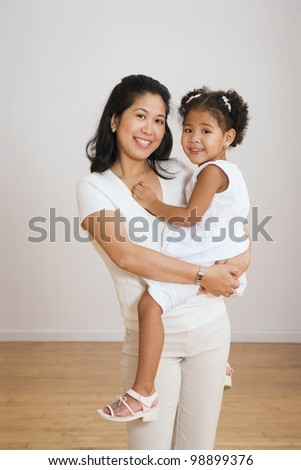 Portrait of Asian mother holding daughter