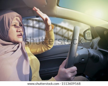 Portrait of Asian muslim female driver get blinded, disturbed dazzled by sun light Stock photo ©