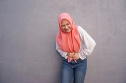Portrait of Asian Muslim girl in hijab hold her stomach feeling pain, menstruation cramp. Abdominal pain concept