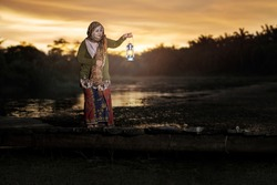 Portrait of asian muslim old lady on wooden jetty with traditional dress and lantern lamp during sunset in rural village
