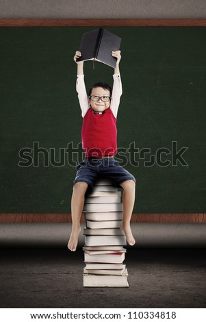Portrait of asian schoolboy holding a book and sitting on a stack of books in front of blackboard