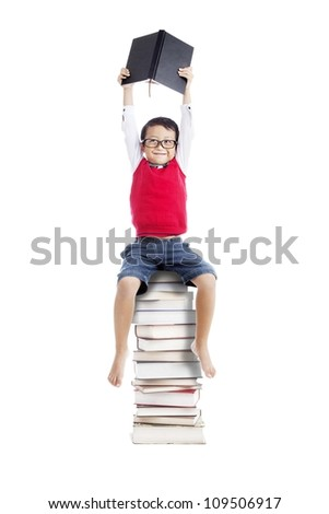 Portrait of asian schoolboy holding a book and sitting on a stack of books isolated on white - stock photo