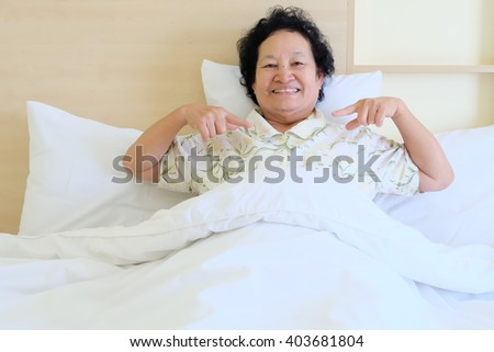 Portrait of Asian senior woman resting on bed #403681804